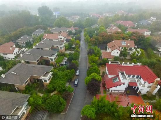 2016年10月23日,郑州一处规划的旅游景区,竟被开发商开发成地产社区,更蹊跷的是,这个违规开发已经存在十年之久,期间郑州市国土局多次对其进行处罚,但至今违规项目依然在建设。子君 摄 图片来源:视觉中国