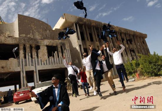 当地时间2016年10月24日,利比亚班加西,班加西大学化学工程专业的学生在战火毁坏的教学楼前拍毕业照。