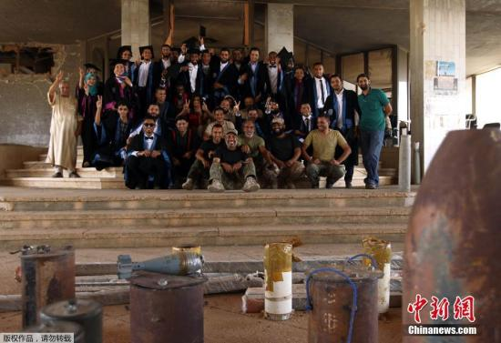 當地時間2016年10月24日,利比亞班加西,班加西大學化學工程專業的學生在戰火毀壞的教學樓前拍畢業照。