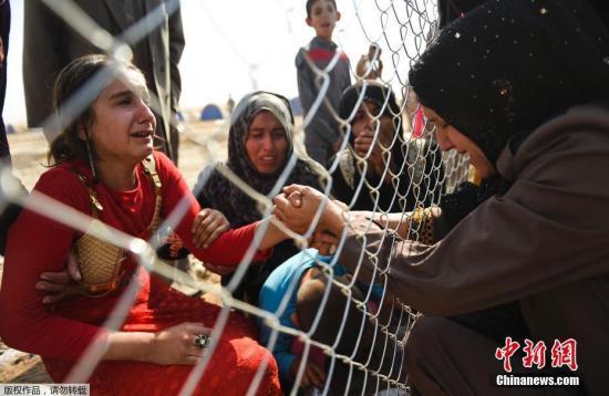 资料图片:难民隔着铁丝网相见。