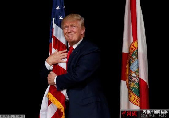 当地时间2016年10月24日,美国佛罗里达州坦帕市,美国共和党总统候选人唐纳德・特朗普在出席拉票活动时拥抱美国国旗。