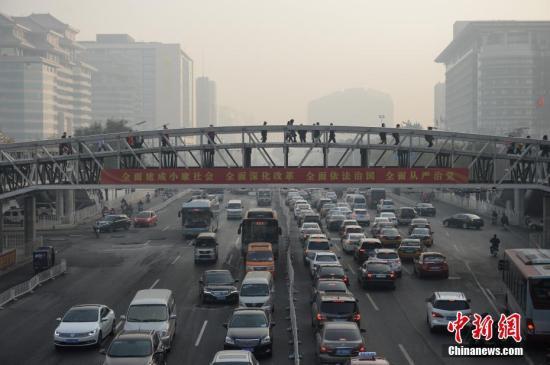 11月3日,北京大气扩散条件转差,空气污染指数持续攀升。据悉,北京已于2日傍晚发布空气重污染黄色预警。根据中国环境监测总站的预测,11月3日至6日,京津冀及周边地区将出现持续静稳天气,不利于大气污染物扩散,部分城市可能出现空气重污染过程。图为午后北京西单商圈逐渐被雾霾笼罩。 中新社记者 崔楠 摄