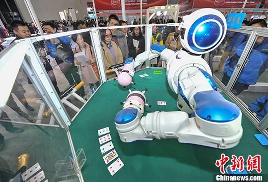 资料图:武汉光博会,可以玩扑克牌的双臂机器人吸引众多参观者。 <a target='_blank' href='http://www.chinanews.com/'>中新社</a>记者 张畅 摄