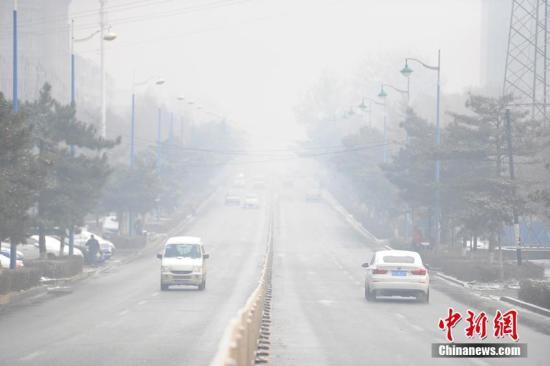 """11月5日,一场""""鹅毛大雪""""将吉林长春""""涂成""""白色,光滑的冰雪路面令交通状况堪忧。与此同时,静稳的大气条件使得连日袭击这里的雾霾无法消散,截至当日8时,长春市区PM2.5浓度达到358微克/立方米,空气质量状况达到污染级别最高的""""严重污染""""。张瑶 摄"""