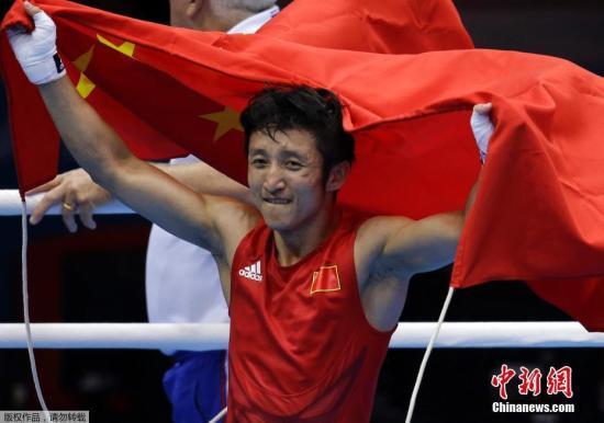 图为2012年伦敦奥运会邹市明拿下自己第二枚奥运会金牌后,手举国旗绕场。