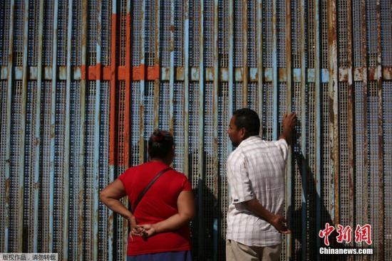 当地时间2016年11月6日,墨西哥提华纳,移民家庭隔着美墨边境之间的隔离墙聊天。