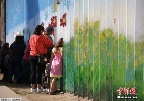资料图:墨西哥提华纳,移民家庭隔着美墨边境之间的隔离墙聊天。