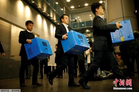 """当地时间2016年11月8日,韩国检方突击搜查了三星电子在首尔的办公室,检察机关有关负责人将扣押物品箱子拿出来。这是围绕韩国总统朴槿惠的密友崔顺实""""干政""""事件调查的一部分。"""