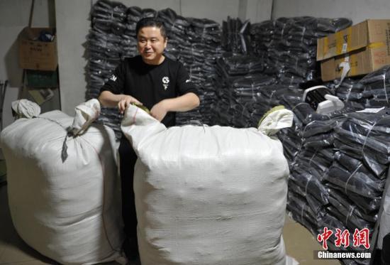 """资料图:成都郫县安靖镇因服装业而兴,因电商成名。去年""""双十一""""该镇千余家服装传统加工厂和淘宝店订单剧增,人手紧张,迎来最忙季。<a target='_blank' href='http://www.chinanews.com/'>中新社</a>记者 刘忠俊 摄"""