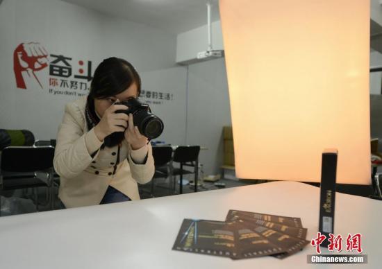 资料图:代购者在简易的摄影棚为代购的产品拍照。杨华峰 摄