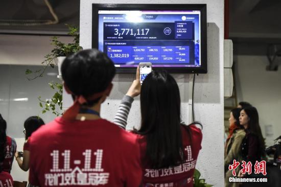 资料图:11月11日,广州海珠创意产业园内的一家电商企业办公室灯火通明,员工关注交易量。11日零时,一年一度的双十一网购狂欢节正式拉开帷幕。