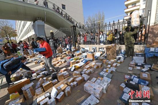 资料图:2016年11月14日,山西太原,山西财经大学校园外摆满各个物流公司发来的快递。图为工作人员忙着分拣满地的快递。 武俊杰 摄