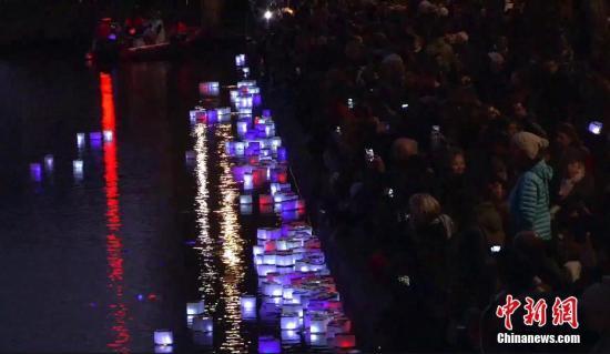 纪念牌、鲜花、气球、蜡烛……2016年11月13日,巴黎系列恐怖袭击一周年之际,法国民众以各种方式,追悼和纪念一年前死于恐怖分子枪击和爆炸的130名逝者。图为巴黎圣马丹运河,