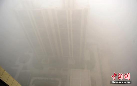 资料图:河北石家庄,被大雾笼罩的楼房。中新社记者 翟羽佳 摄