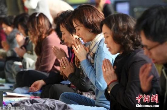 当地时间11月16日,韩国高考临近,考生家长在位于首尔的佛教寺庙内点蜡烛许愿祈福。