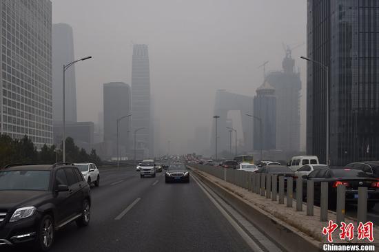 资料图:北京民众在雾霾中出行。/p中新网记者 金硕 摄