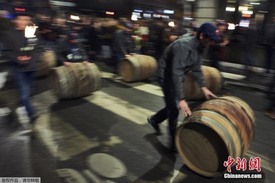当地时间2016年11月17日,法国里昂,酿酒人将装着博若莱新酒的酒桶滚上街头,开桶请民众品尝。从上世纪70年代开始,每年11月的第3个星期四,博若莱新酒全球统一开瓶。一般葡萄酒不会当年产当年喝,所以这种可以称为是世界上独一无二葡萄酒的开瓶日,成为全球爱酒人士的盛宴 。