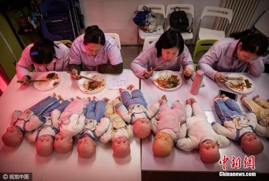北京,妇女们参加阿姨大学的月嫂培训课程。图片来源:视觉中国
