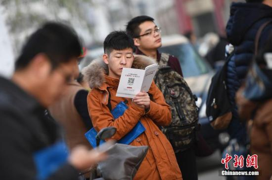 """11月27日,山西太原,参加2017年中国国家公务员考试的考生在考前紧张复习。当日,有""""国考""""之称的中国国家公务员招录公共科目笔试开考。据中国国家公务员局统计,2017年国家公务员考试最终有148.63万人通过报名资格审查,较去年增加9.17万人,国考报名在连续两年""""降温""""后又再度""""升温""""。中新社记者 韦亮 摄"""