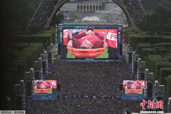 當地時間2016年7月10日,法國巴黎,球迷在埃菲爾鐵塔觀看歐洲杯決賽,法國對陣葡萄牙,C羅在比賽中受傷,被擔架抬出場外。