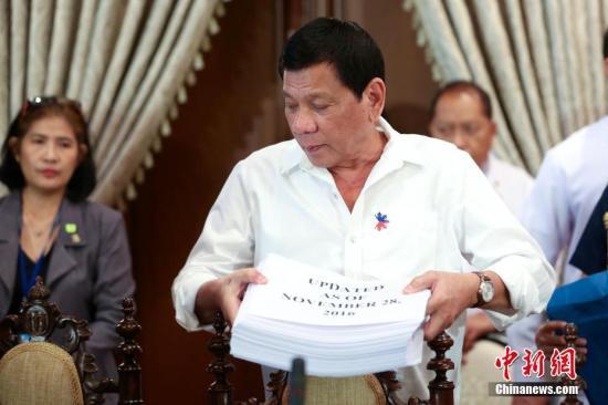 12月5日,菲律宾杜特尔特召开内阁会议。图为杜特尔特在会上向内阁成员展示一大摞包含涉嫌参与毒品犯罪活动官员和警察名单的资料。杜特尔特今年6月30日出任总统后,立即在全国范围内开展声势浩大的禁毒行动,他之前曾数度对外公开涉毒官员和警察名单。   中新社记者 malacanang 摄