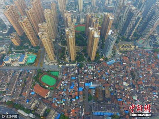 """2016年12月07日,上海,航拍上海最大的棚户区——张桥,航拍镜头下,低矮的棚户区密密麻麻,与周边的高端楼盘形成了鲜明的对比。据悉,该棚户区没有物业,全靠居委,住着1965户、3382人,居住条件窘迫,卫生设施缺乏,90%的居民还在""""倒马桶"""",有时连基本的水、电使用都不顺畅,而周边新建造的瑞虹新城、建邦十六区等高端楼盘均价都在10万左右,据悉,该地块已经开始旧改征询,动迁在望。蒋一超 摄 图片来源:视觉中国"""