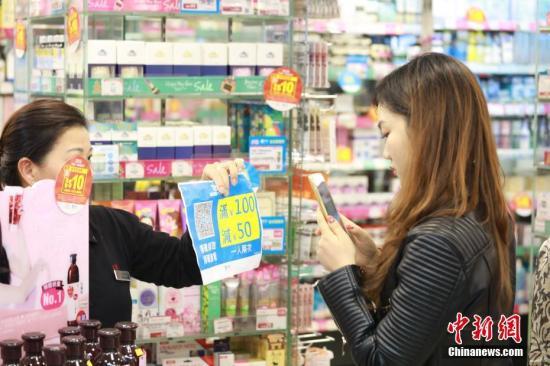 """香港店员随身备着一张打印好二维码,让消费者扫码拿""""双12""""优惠。香港商店里全是排队用支付宝参加""""双12""""的人。截止10日24点,""""双12""""全球狂欢节有接近30万人次境外刷支付宝,同比增长3倍,全球数百个商家门店创出了移动支付交易纪录。"""