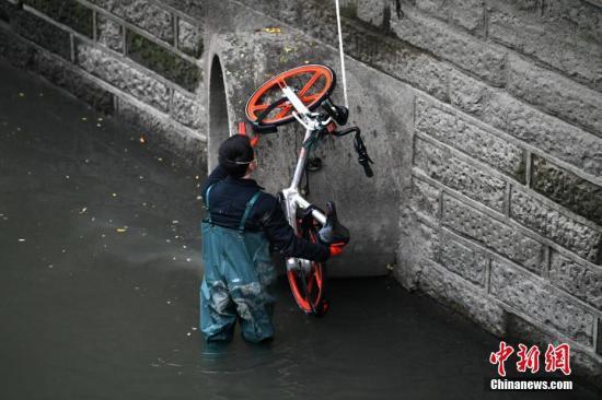 资料图:一辆共享单车被扔进成都锦江,工作人员冒着寒冬下水将其打捞上岸。张浪 摄