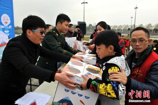 万载县义工联合会会长李春平(左一)在为贫困学生发放爱心温暖包。 邓龙华 摄