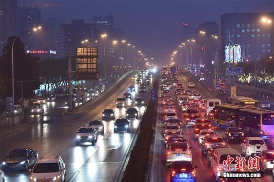 12月15日,北京发布今年首个空气重污染红色预警――今日20时,本市启动空气重污染红色预警。本市提前约30个小时发布红色预警,各相关单位提前做好准备,应对空气重污染。图为12月16日傍晚,北京东三环国贸桥雾霾笼罩。记者 金硕 摄