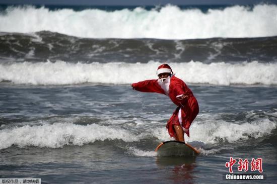 """资料图:印度尼西亚巴厘岛上的工作人员打扮成""""圣诞老人""""教授少年学习冲浪技巧。"""