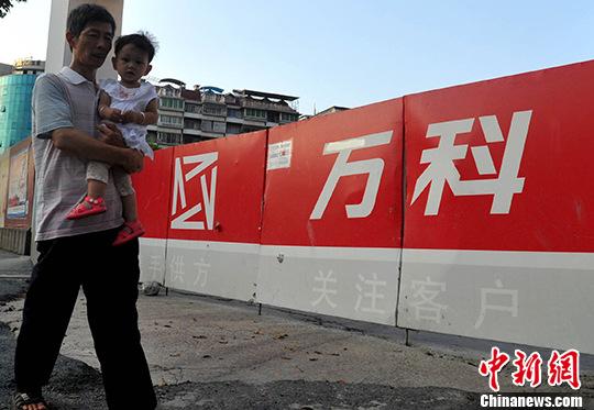 资料图:民众从万科楼盘工地旁经过。(资料图片) <a target='_blank' href='http://www.chinanews.com/'>中新社</a>记者 张斌 摄
