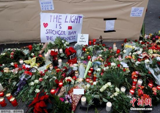 当地时间2016年12月20日德国柏林民众在恐袭事发点附近摆满鲜花。19日晚德国首都柏林一辆重型卡车冲入圣诞市场人群。据警方最新消息此次事件已经导致12人死亡48人受伤。