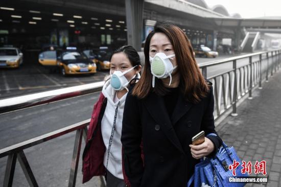资料图:北京重污染天气过程持续。图为旅客佩戴口罩前往首都机场。记者 崔楠 摄