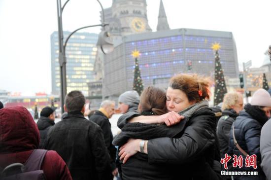 当地时间12月20日下午,德国柏林民众自发聚集到前一天晚间遭遇卡车恐袭的布赖特沙伊德广场圣诞市场前,表达对逝者的哀思。袭击已造成12人遇难,近50人受伤。图为现场一名女子在安慰难抑哀恸的友人。 <a target='_blank' href='http://www.chinanews.com/'>中新社</a>记者 彭大伟 摄