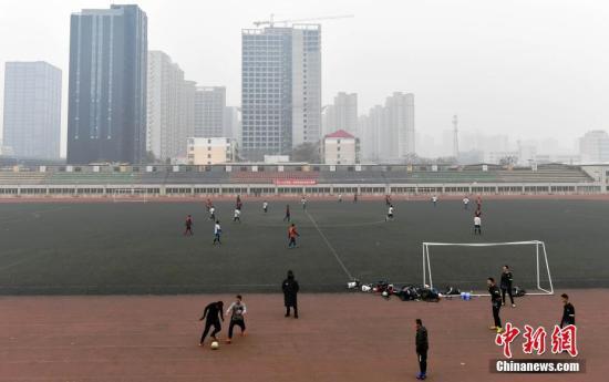 12月25日,河北石家庄一大学内的体育场上,一群足球爱好者正在霾中踢足球。当日,河北省气象台继续发布霾黄色预警。   中新社记者 翟羽佳 摄