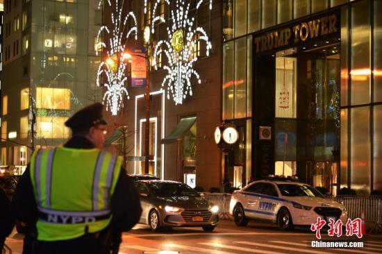 当地时间12月27日晚,纽约特朗普大厦出现可疑包裹。纽约警方对周边民众进行紧急疏散,并派拆弹小组前往,经排查后已确认可疑包裹内的物品为玩具。图为在特朗普大厦附近街口执勤的纽约警察。 /p发 袁月明 摄