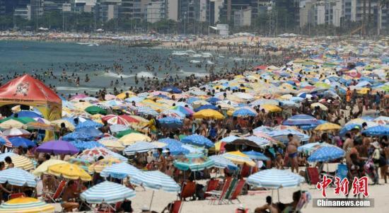 资料图:巴西里约,人们聚集在伊帕内玛海滩游泳和晒日光浴。