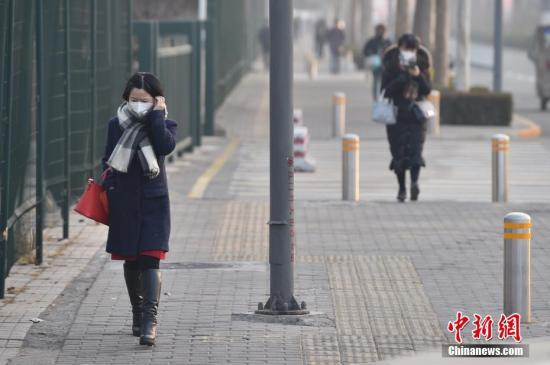 资料图:民众戴口罩出行。/p记者 金硕 摄