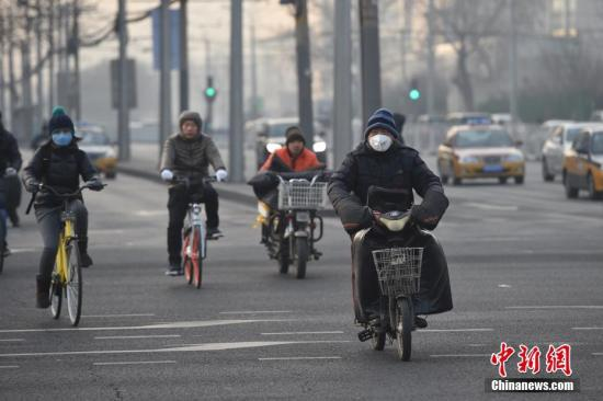 """2016年12月30日,北京处于中重度空气污染,市民""""戴口罩""""出行。北京29日下午发布消息,将从2016年12月30日零时至2017年1月1日24时启动空气重污染橙色预警。""""这次重污染过程持续时间长。""""中国环境监测总站预报中心值班预报员王威介绍说,从29日晚上开始,京津冀及周边地区的污染过程可能持续到2017年1月6日。 中新网记者 金硕 摄"""