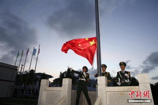 1月1日清晨,海南省三沙市同时在南海9岛礁及相关船舶上举行元旦升国旗仪式。靠泊的三沙市综合执法1号船,在南沙从事渔业生产的渔船也同时举行了升旗仪式。图为三沙市政府所在永兴岛上的升旗仪式。 <a target='_blank' href='http://www.chinanews.com/'>中新社</a>发 吴亚铁 摄