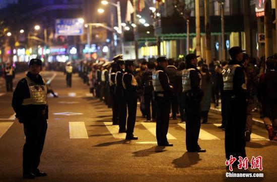 资料图:12月31日晚,上海警方加强外滩、南京路步行街等公共场所的警力。当日,上海警方启动一级加强勤务等级,5万警力全员上岗,确保跨年夜民众出行安全。 中新社记者 汤彦俊 摄