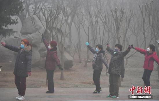 资料图:2017年1月2日,在河北石家庄一公园,一群大妈正戴着口罩运动健身。该省继续发布大雾橙色预警和霾橙色预警,多个城市空气严重污染。 中新社记者 翟羽佳 摄