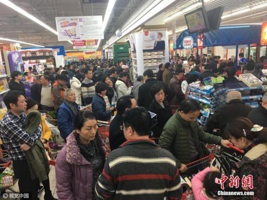 资料图:南京一超市打折, 顾客蜂拥而至抢空货架。 图片来源:视觉中国