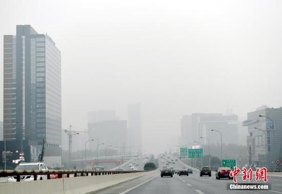 资料图:图为汽车在雾霾中穿行。中新社记者 安源 摄