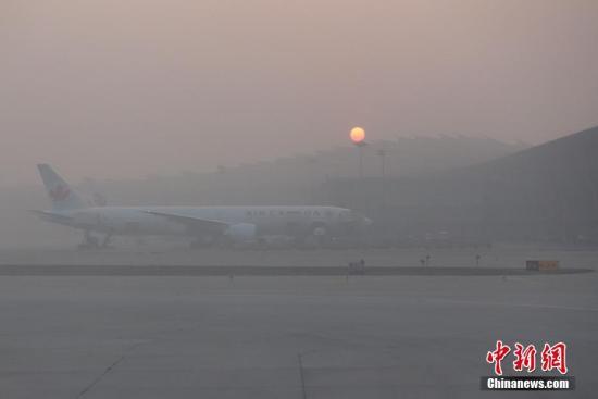 资料图 1月3日,雾霾笼罩下的北京首都机场。中新社记者 崔楠 摄