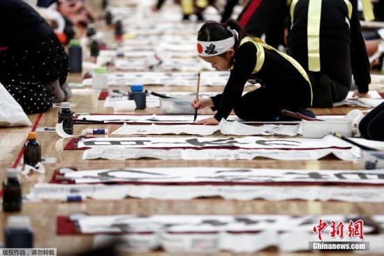 当地时间1月5日,日本民众在东京参加新年书法比赛。日本儿童参加比赛。