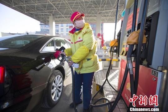 资料图,加油站工作人员正在给车辆加油。 张云 摄