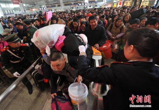 """1月13日,福州火车站乘坐首趟K4186次""""定制专列""""的返乡旅客在检票上车。 张斌 摄"""