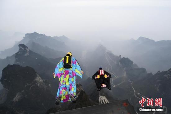 """资料图:1月16日,张家界天门山顶的温度已降至零度以下,""""中国飞人""""张树鹏与加拿大""""翼装侠""""格雷厄姆・迪金森从山顶一跃而下,进行竞速较量。 杨华峰 摄"""